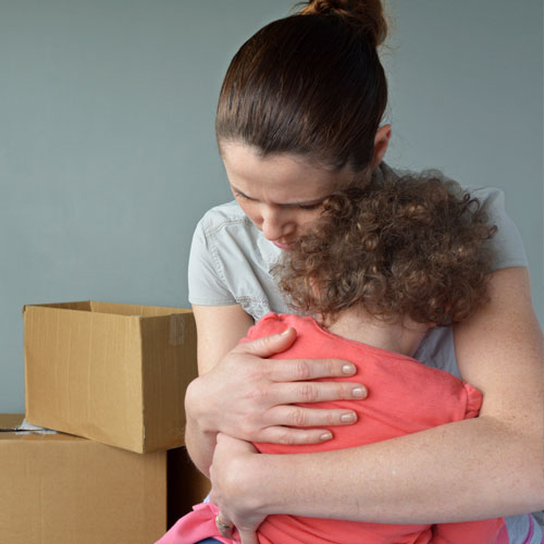 Woman hugging child and crying because of eviction